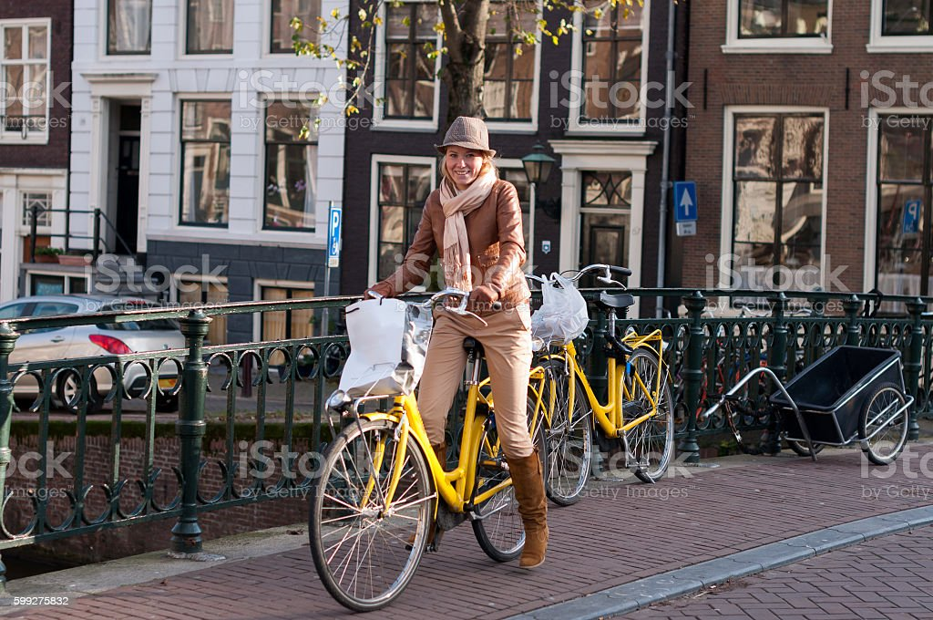 Young beatiful woman with bicycle In Amsterdam stock photo
