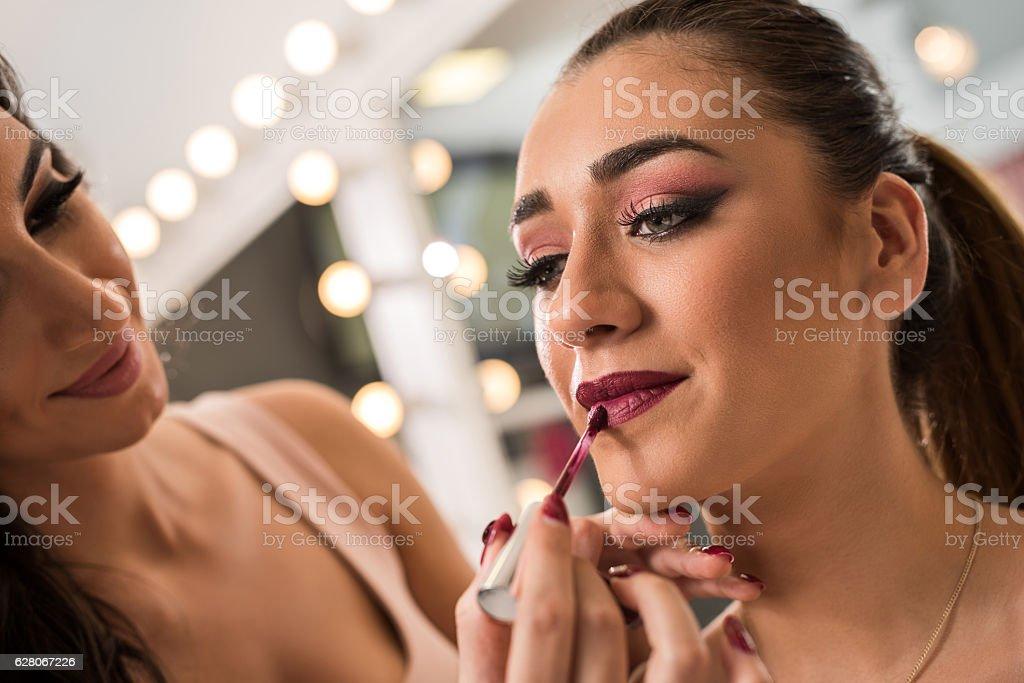 Young beautician applying lip balm on beautiful woman. stock photo