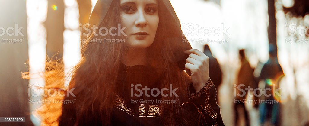 Young beautiful and mysterious woman in woods, in black cloak stock photo