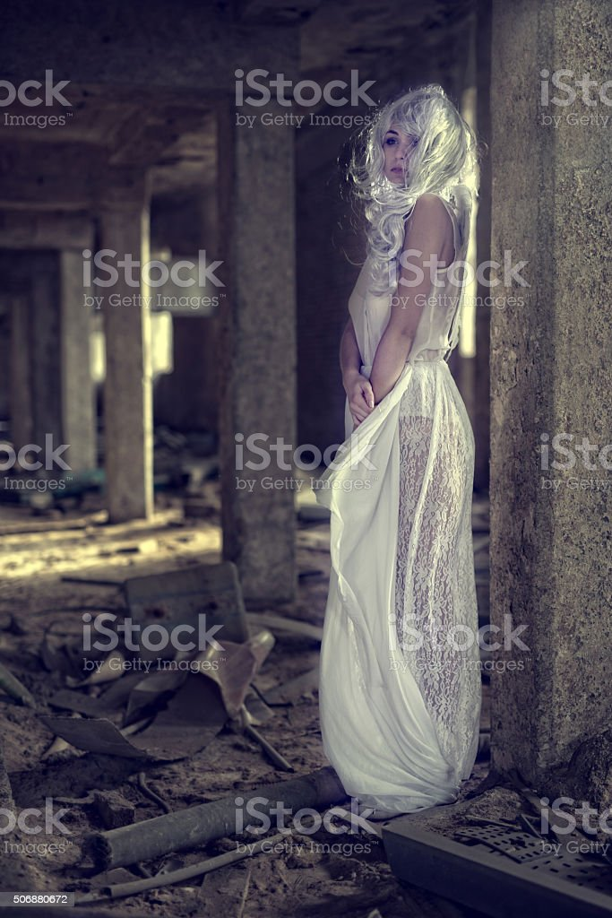 Young beautiful angel in white dress standing in a ruin. stock photo