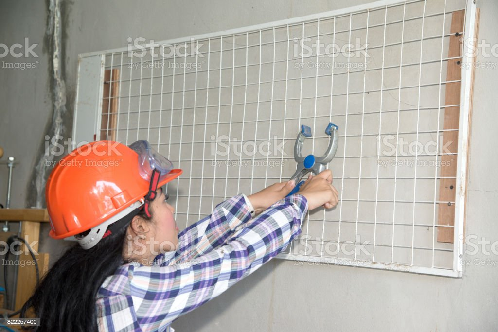 Young beautiful Asian woman holding and install white plastic mesh. stock photo