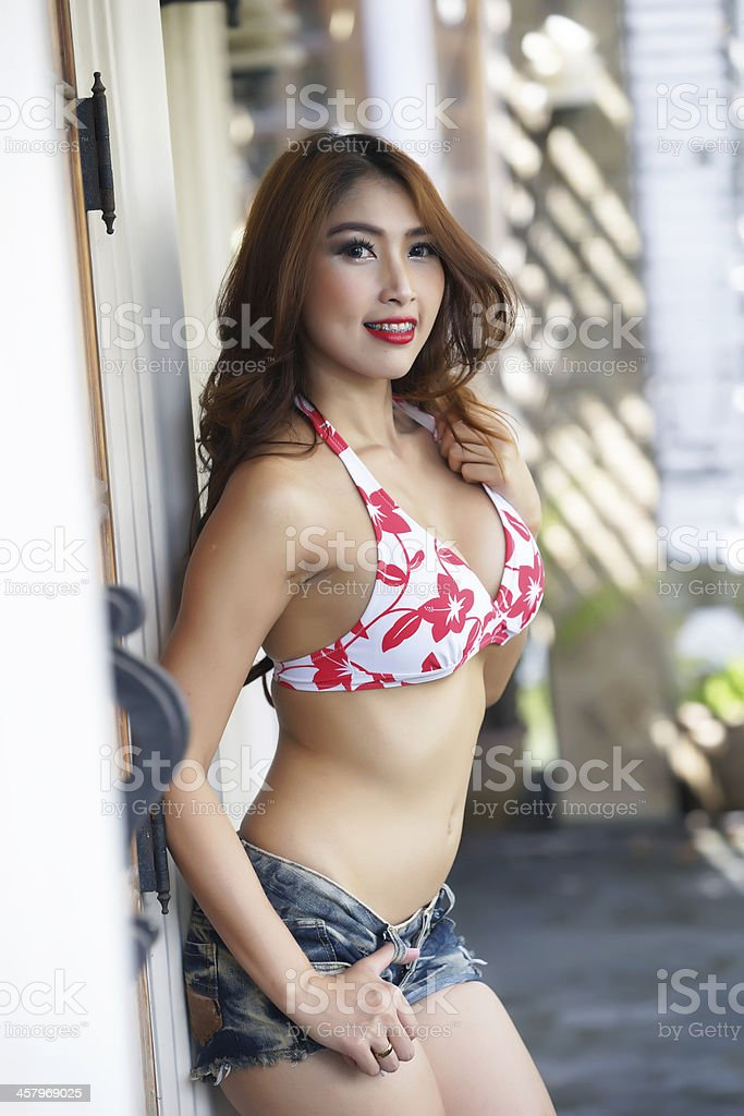 Young beautiful Asian woman in red bikini with short pants stock photo