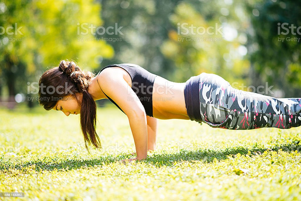 Young beautiful athlete woman doing push ups in outdoor training stock photo