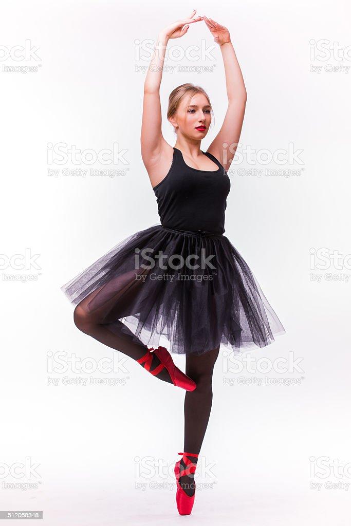 Young beautiful ballerina dancer posing on a studio background. stock photo