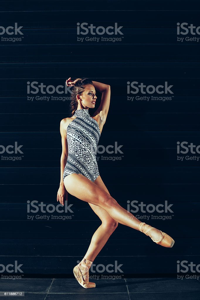 Young beautiful ballerina posing at night next to the futuristic stock photo