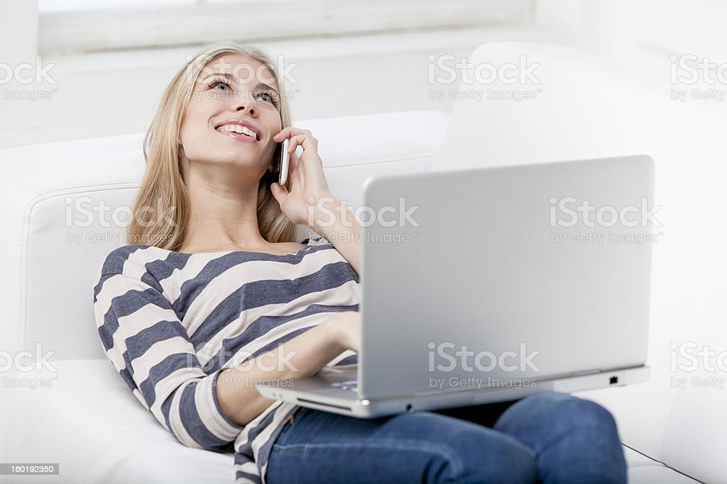 young beautiful blond woman laying on the couch with laptop royalty-free stock photo