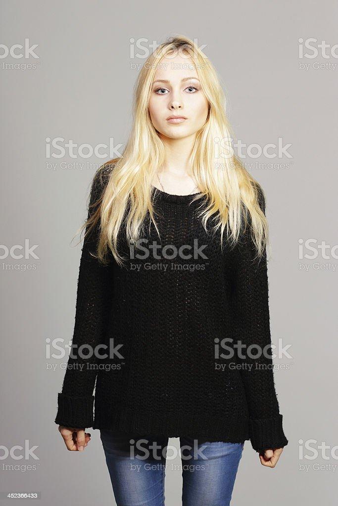 Young beautiful blonde girl in black sweater stock photo