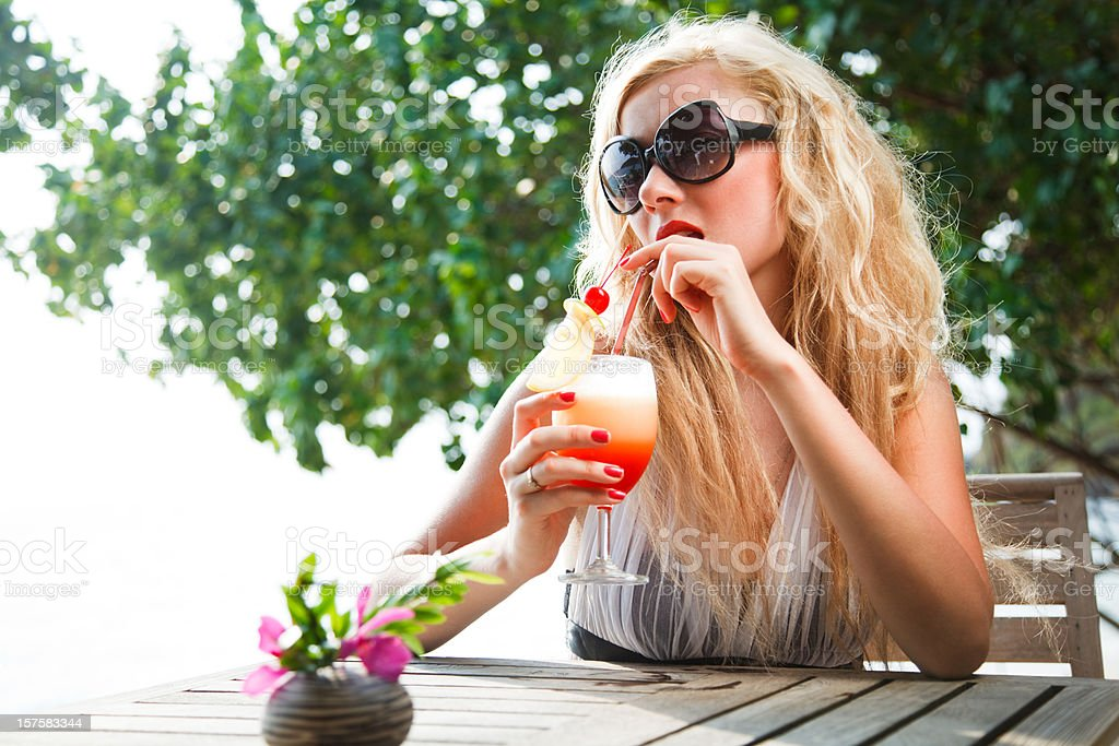 young beautiful blonde woman drinking cocktail royalty-free stock photo