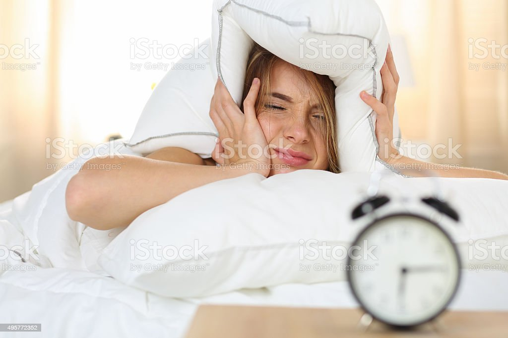 Young beautiful blonde woman lying in bed stock photo