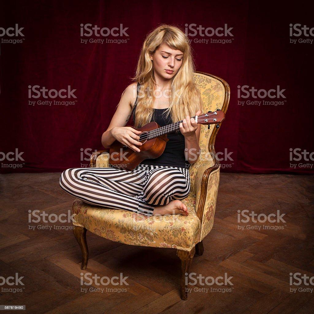 young beautiful blonde woman playing ukulele on a vintage sofa stock photo