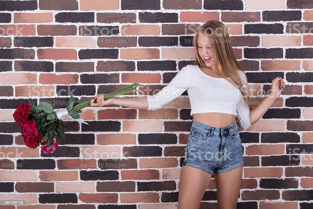 Young beautiful blong girl throws roses out stock photo