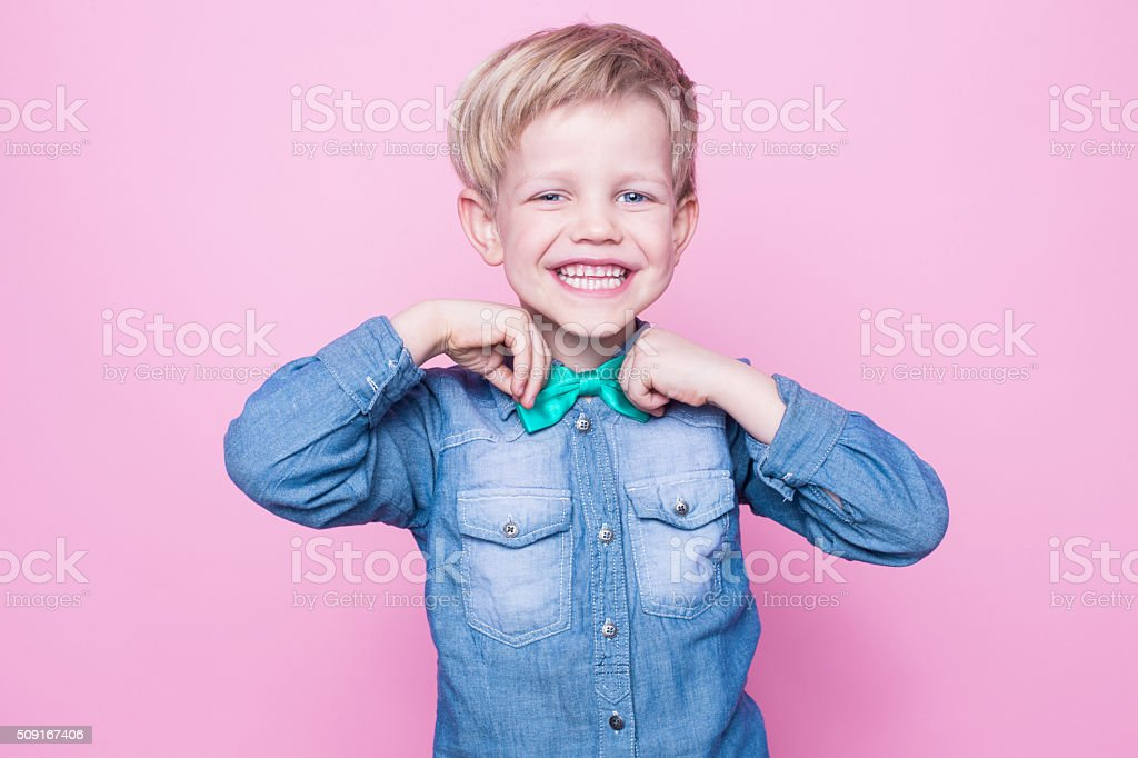 Young beautiful boy with blue shirt and butterfly tie stock photo