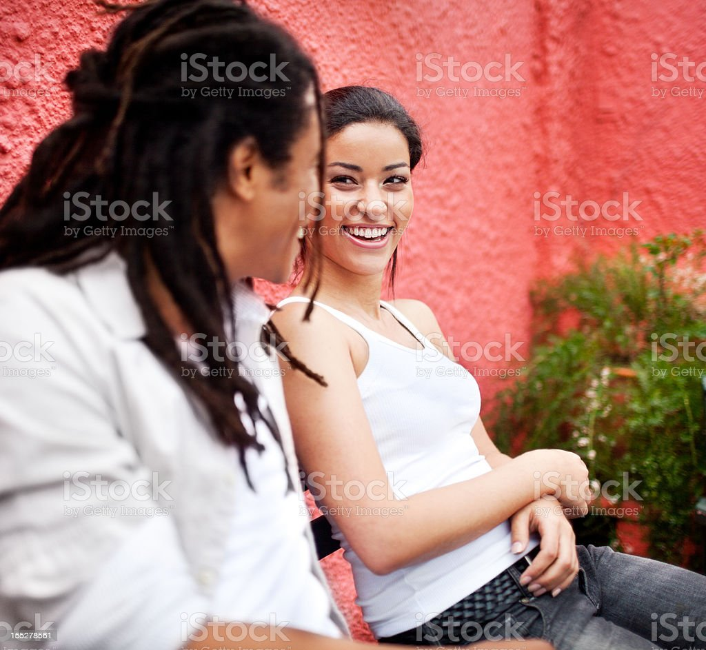 Young beautiful brazilian couple enjoying each other's company on bench. royalty-free stock photo