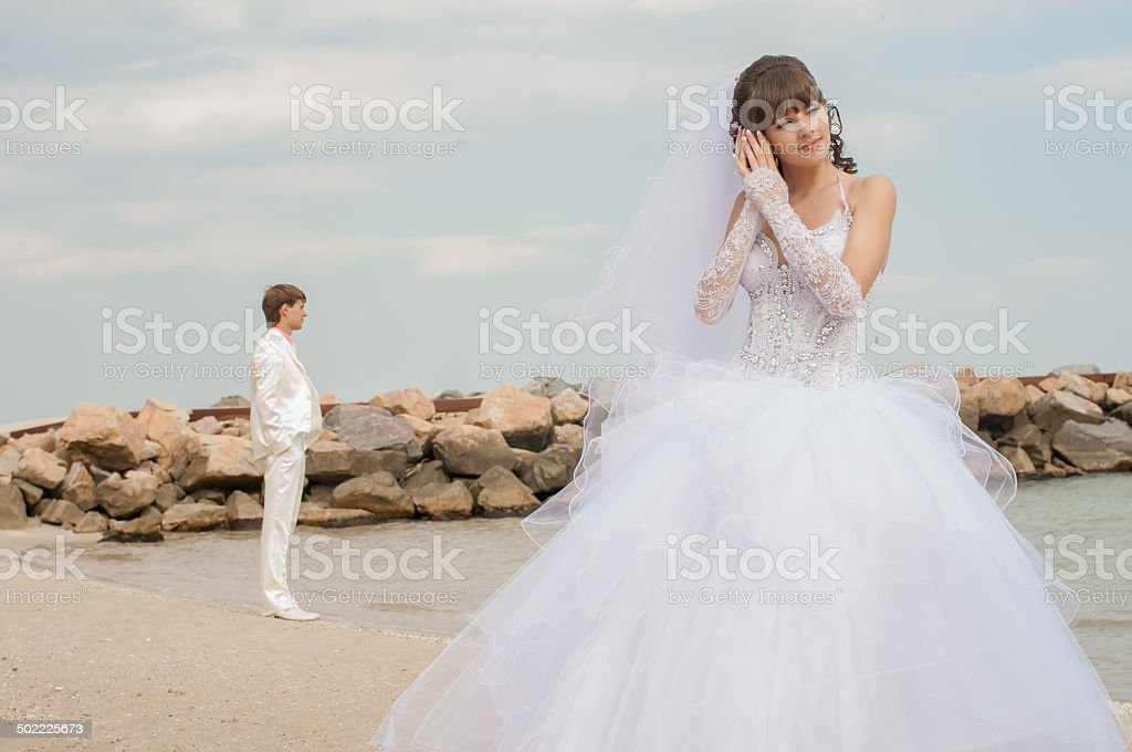 Young beautiful bride on the beach with seashell stock photo