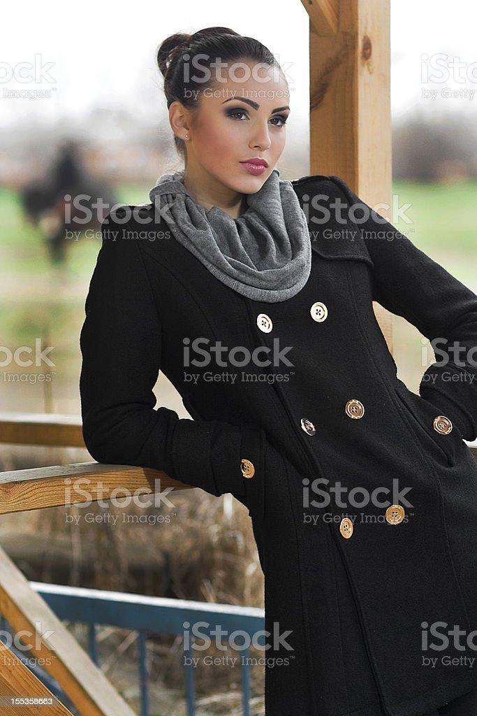 Young beautiful brunet fashion model in dark coat. Street shot royalty-free stock photo