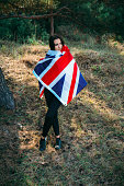 Young beautiful brunette girl posing with a British flag
