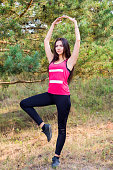 Young beautiful brunette tying shoes while jogging
