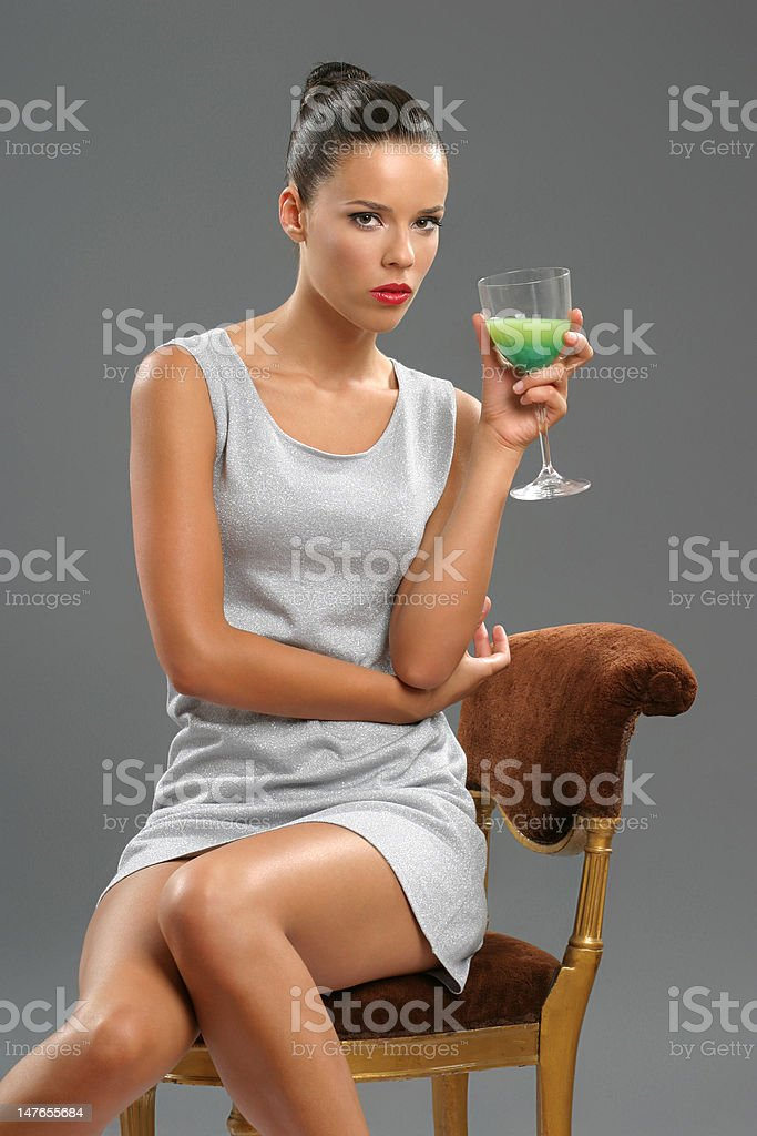 Young beautiful casual girl holding a coctail on gray royalty-free stock photo