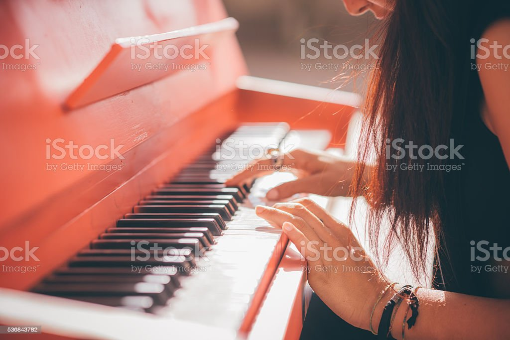 Young beautiful caucasian girl playing piano stock photo