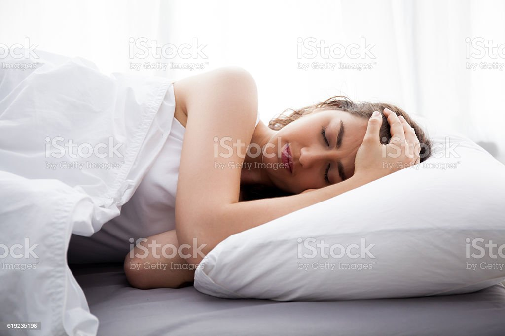 Young beautiful Caucasian woman on bed having headache stock photo