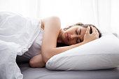 Young beautiful Caucasian woman on bed having headache