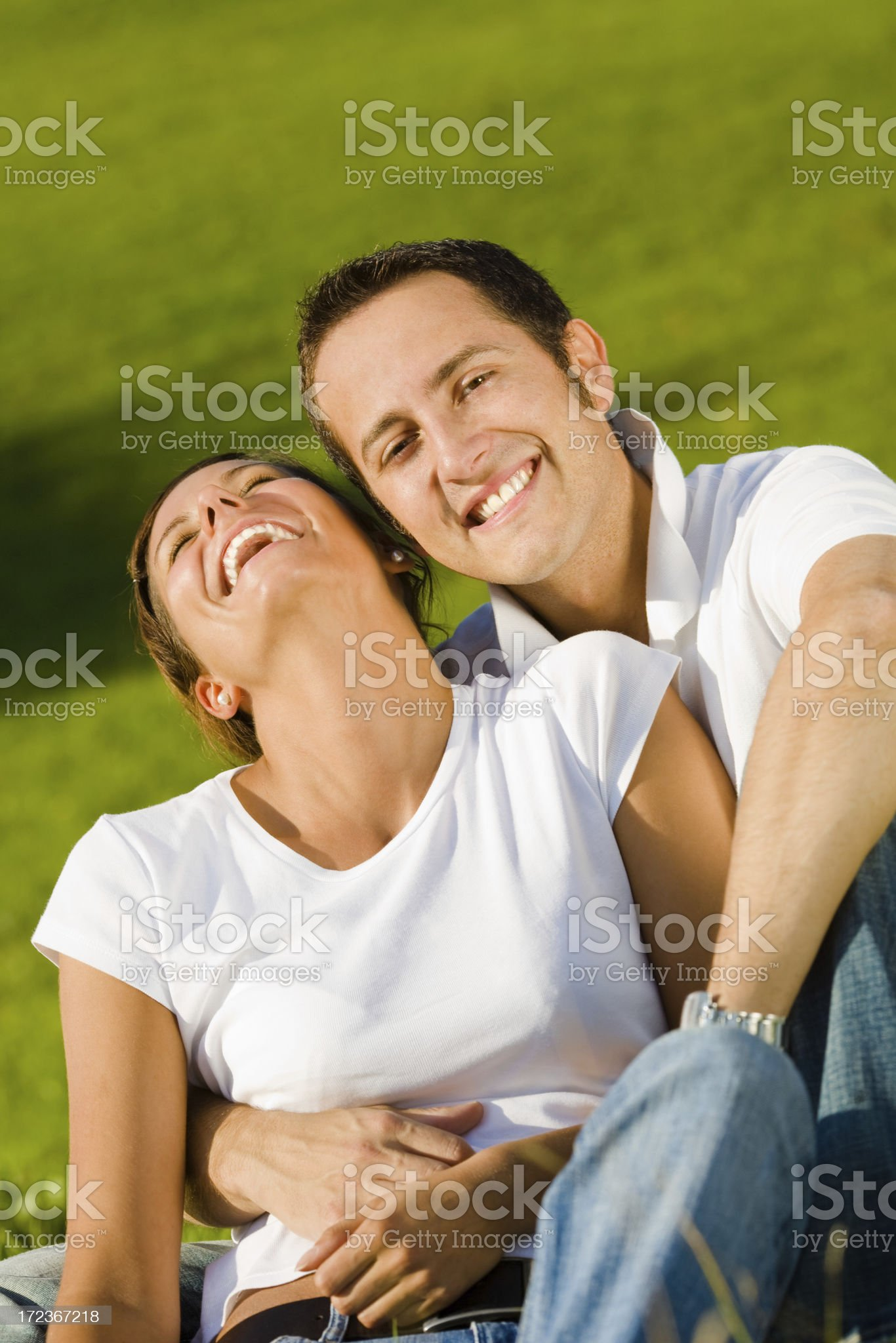 young beautiful couple laughs and hugs in grass field royalty-free stock photo