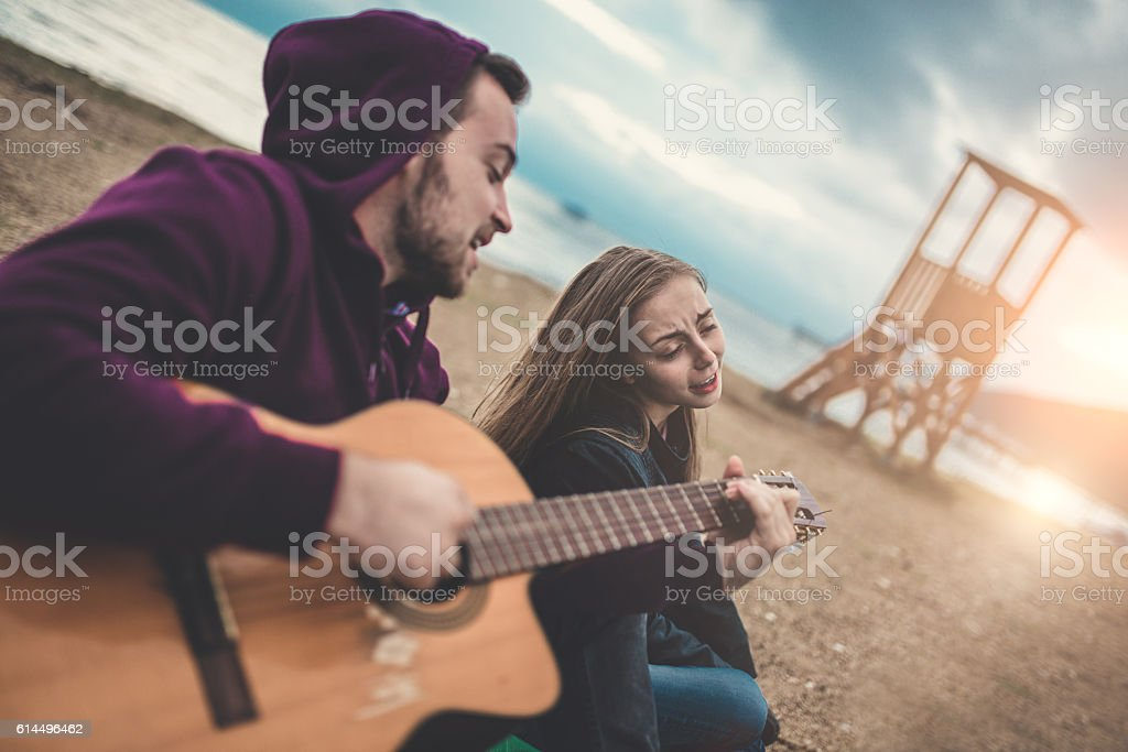 Young Beautiful Couple with Acoustic Guitar Singing at Beach Party stock photo