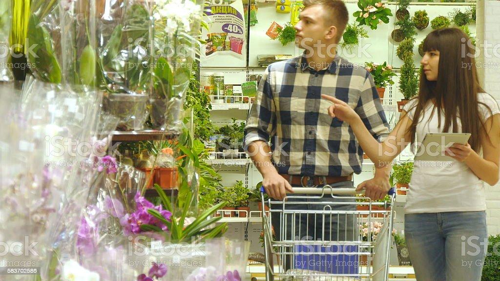 Young beautiful couple with supermarket trolley are walking and choosing foto de stock libre de derechos