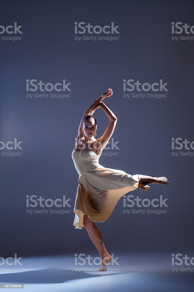 Young beautiful dancer in beige dress dancing on gray background stock photo