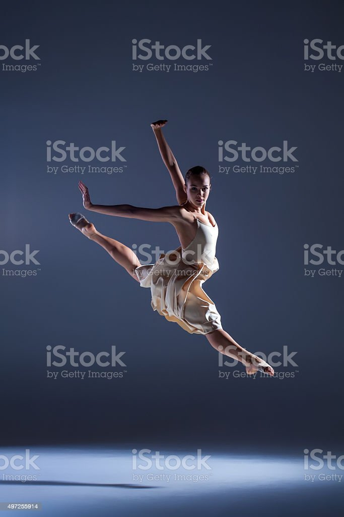 Young beautiful dancer in beige dress jumping on gray background stock photo