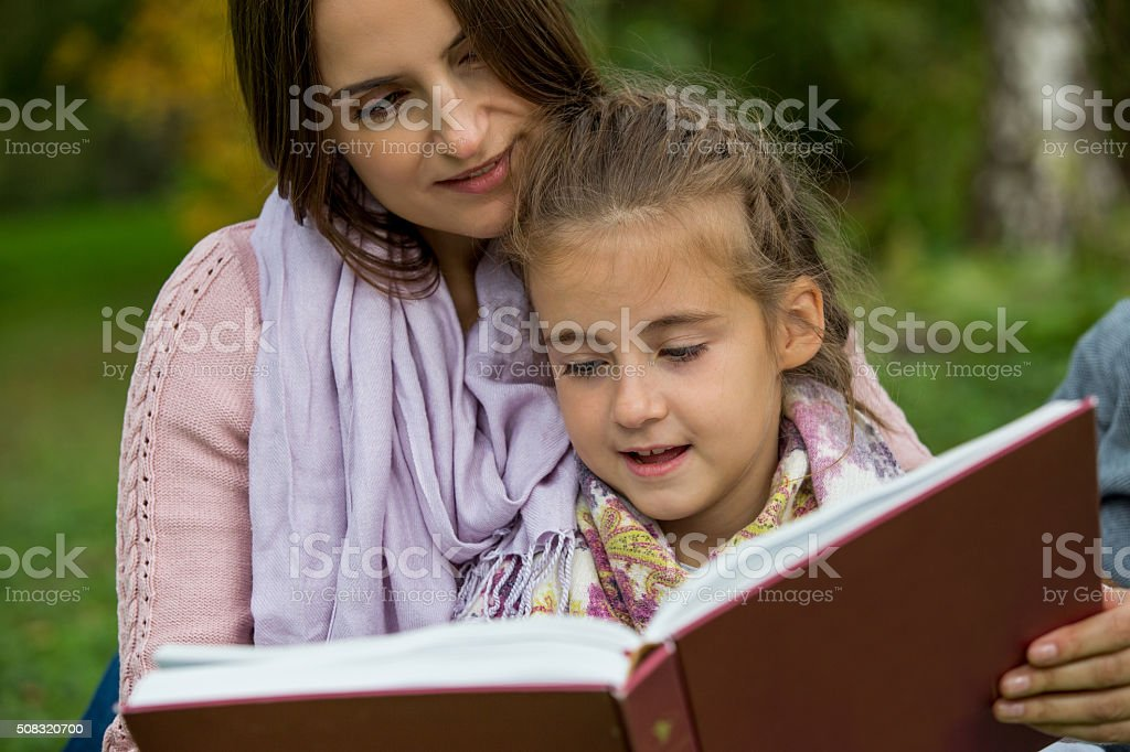 Young beautiful family sitting with big book stock photo