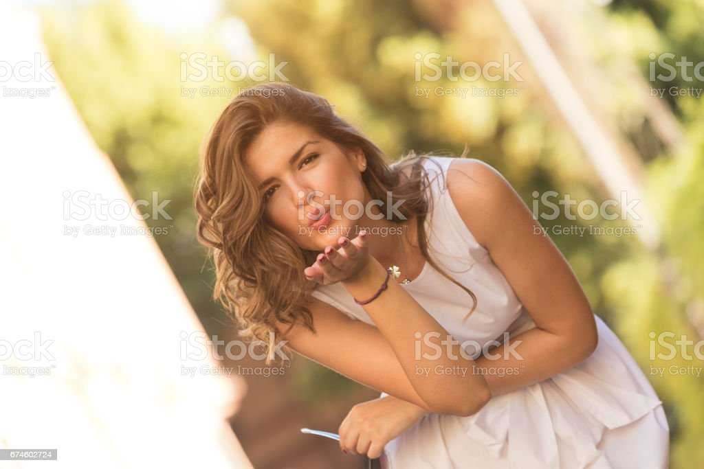Young beautiful fashionable girl sending air kiss on the street. stock photo