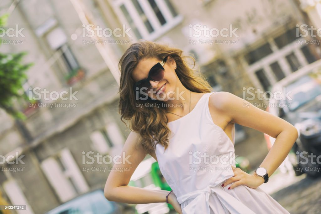 Young beautiful fashionable woman posing on the street. stock photo
