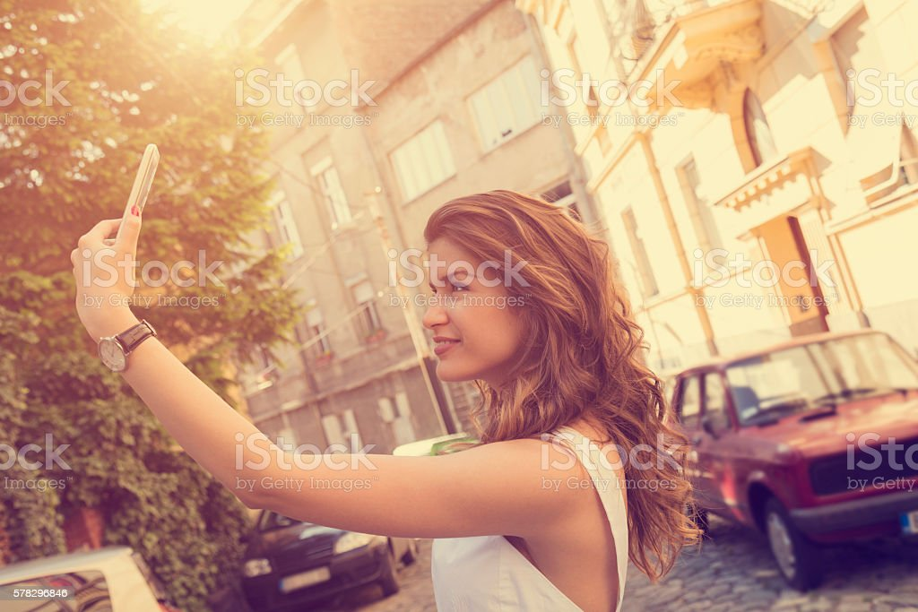 Young beautiful fashionable woman using cellphone outdoors. stock photo