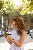 Young beautiful fashionable woman using cellphone outdoors.