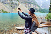 Young beautiful female backpacker doing pictures on her phone