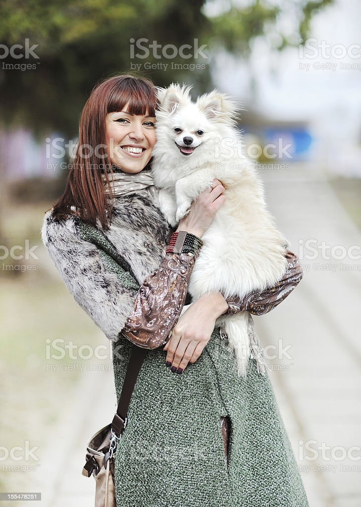 Young beautiful female holding her little puppy and smiling outdoors royalty-free stock photo