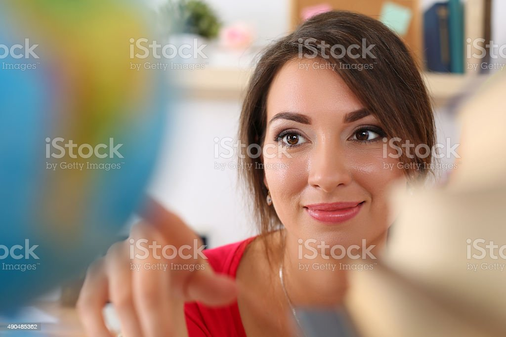 Young beautiful female student pointing something on globe stock photo
