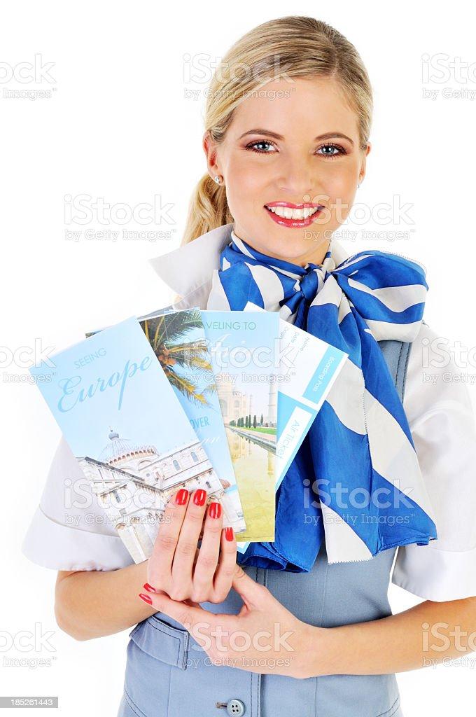 Young beautiful flight attendant showing catalogs stock photo