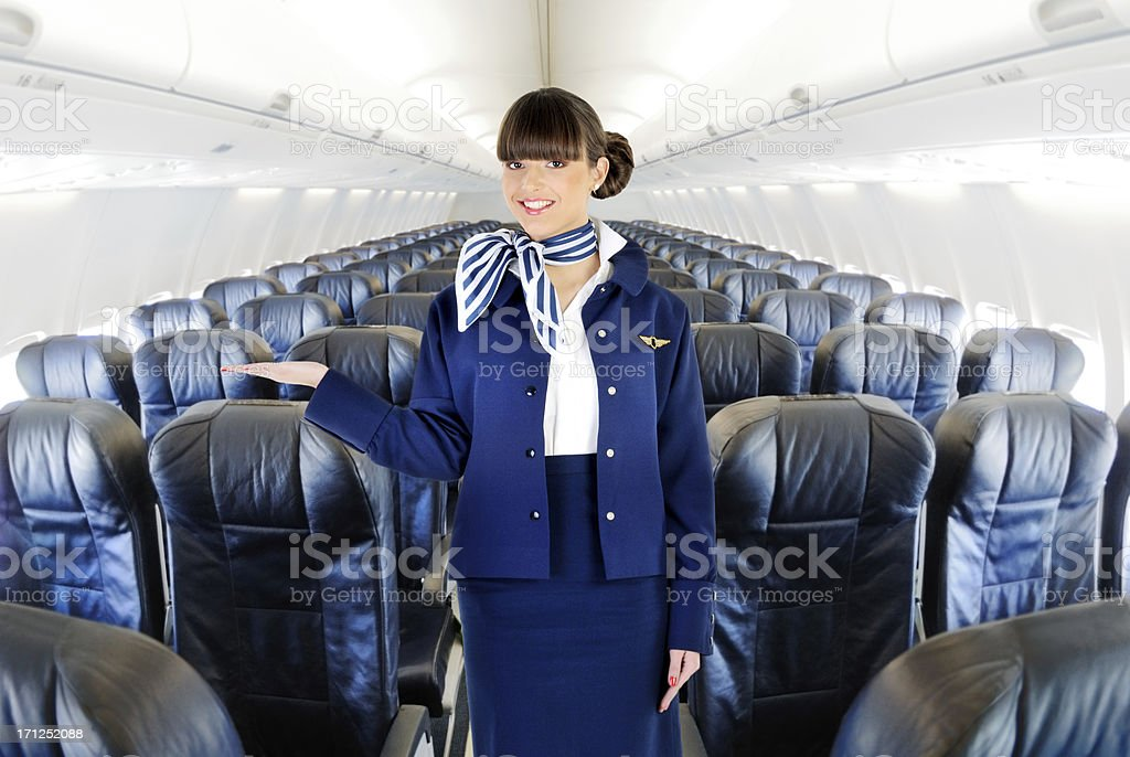 Young beautiful flight attendant welcome stock photo