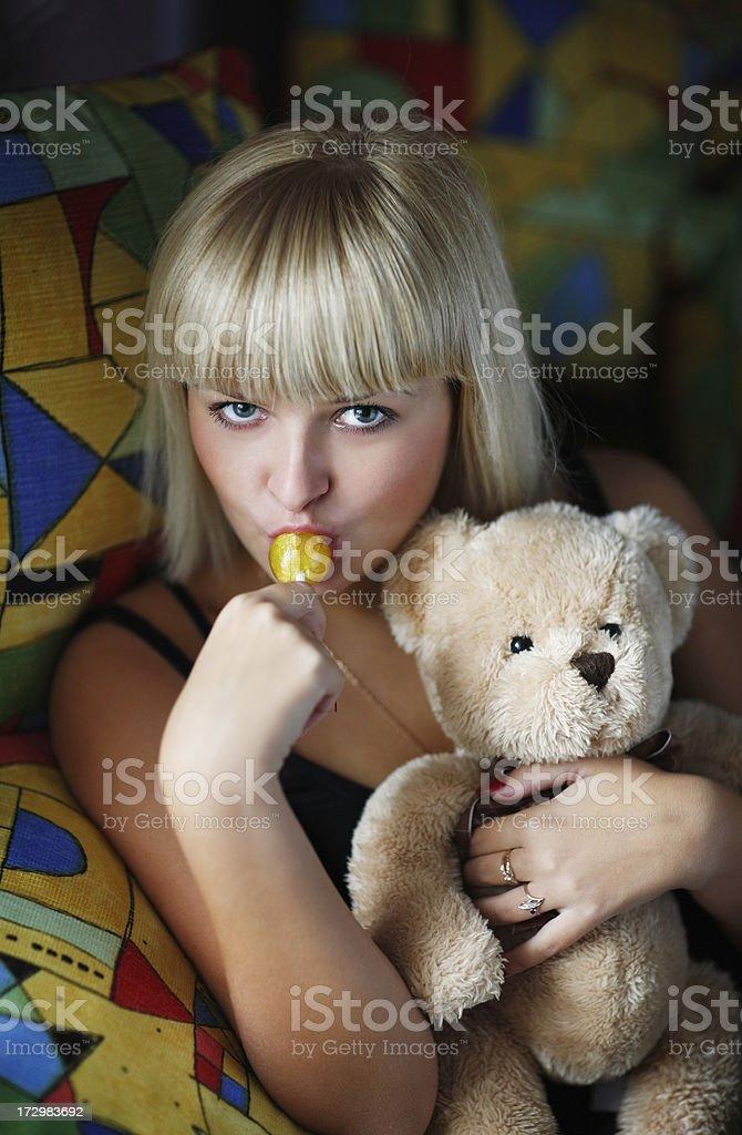 Young beautiful girl eats a sugar candy royalty-free stock photo