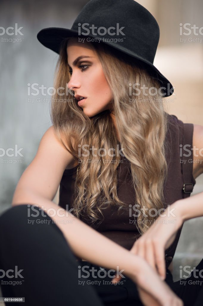 Young beautiful girl in a short elegant top and black hat stock photo