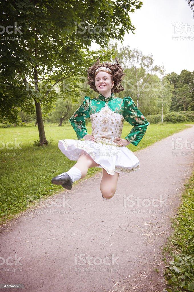 Young beautiful girl in irish dance dress jumping outdoor stock photo
