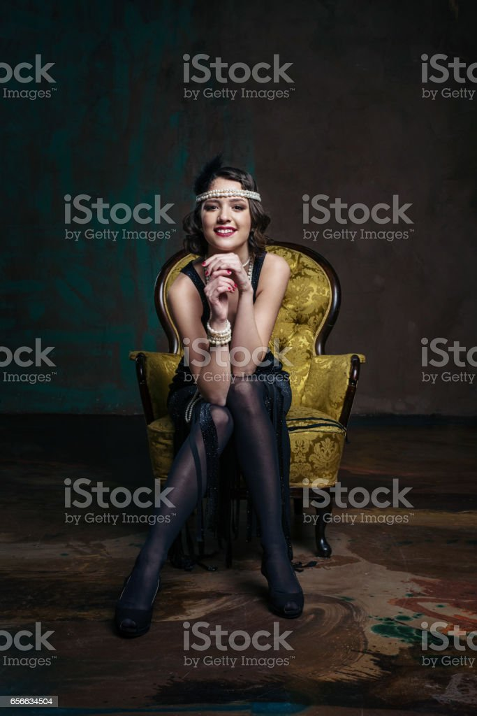 Young beautiful girl in red dress style of the 20's or 30's with glass of martini near the piano. Vintage style beautiful woman. Old fashioned makeup and retro finger wave hairstyle. stock photo