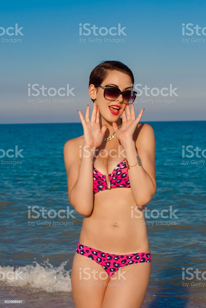 Young beautiful girl in swimsuit at the beach stock photo