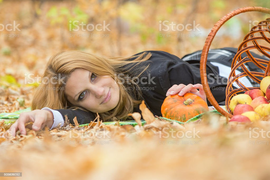 Young beautiful girl lies on foliage in autumn forest stock photo