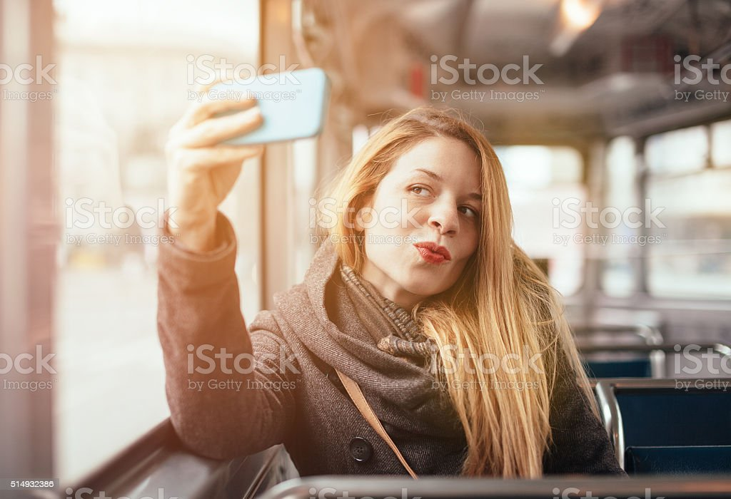 Young beautiful girl posing in the train with phone stock photo