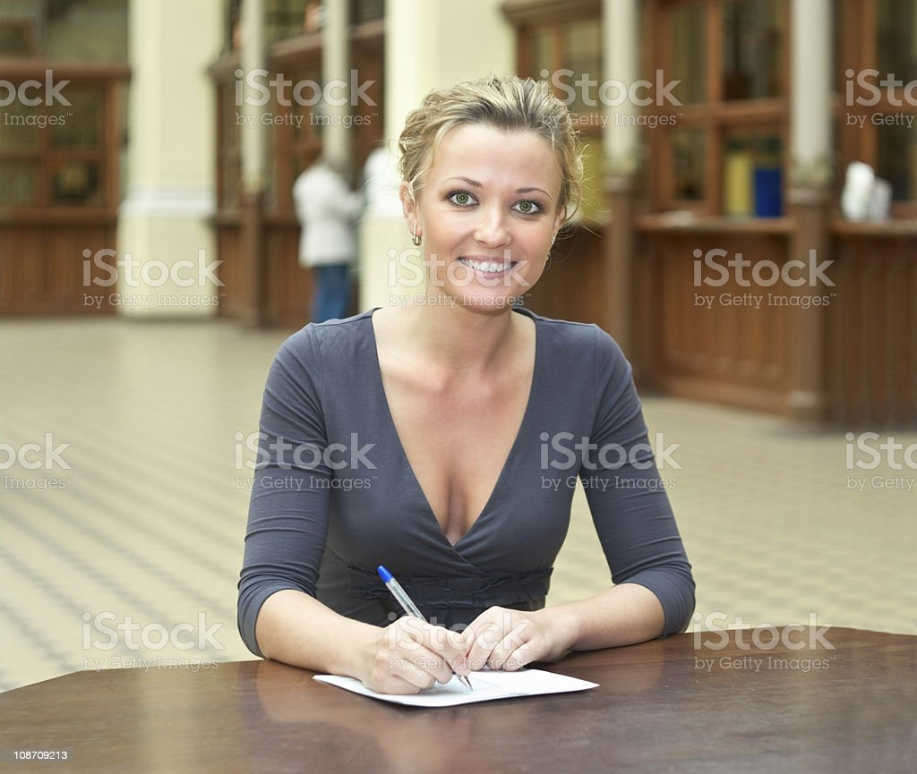 Young beautiful girl sitting fills out a form royalty-free stock photo