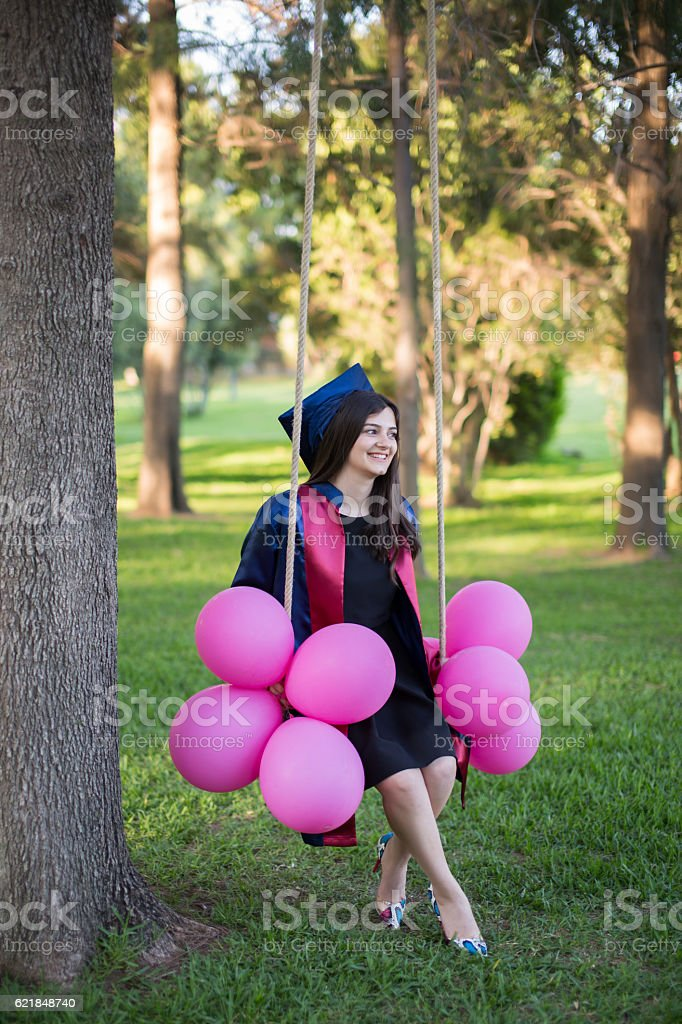 Young beautiful graduate girl with baloons in the field stock photo