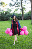 Young beautiful graduate girl with baloons in the field